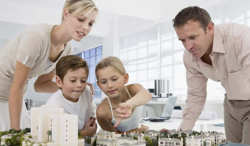 Family looking at property model