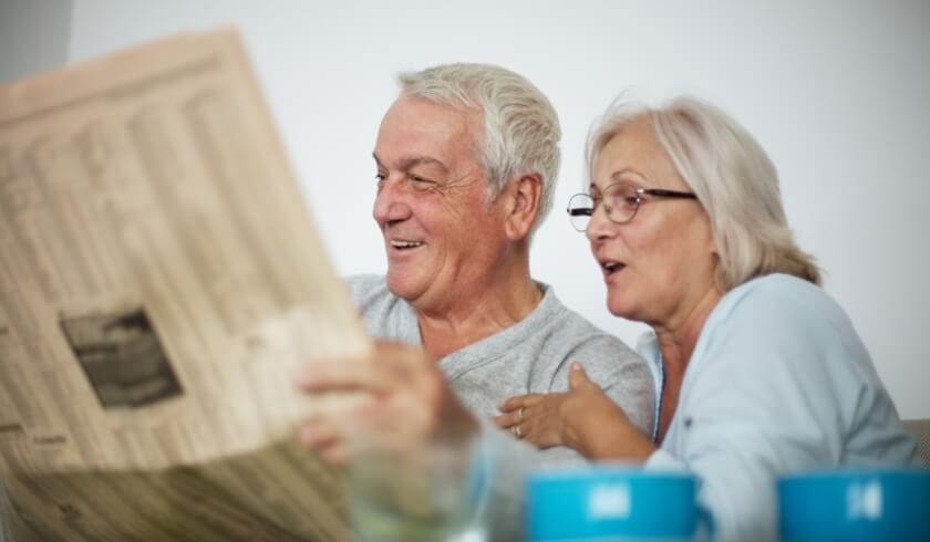 Two retirees reading a newspaper together