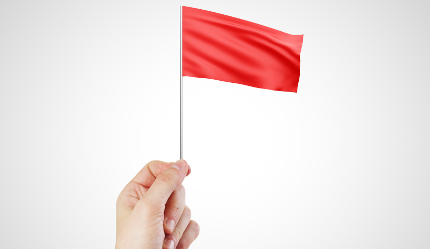 A hand holding a red flag