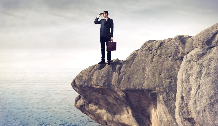 A man in a suit looks off the edge of a cliff with binoculars