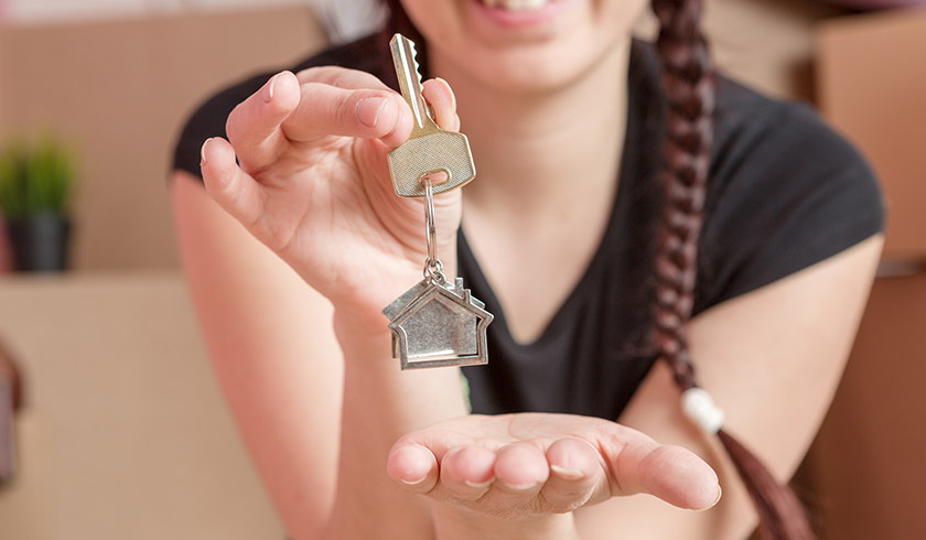 Millenial woman holding house key